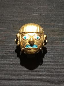 金地に象嵌(ぞうがん)された人面形の装飾品